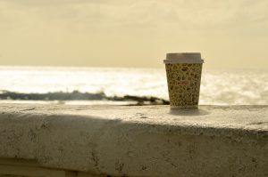 disposable coffee cup by the beach