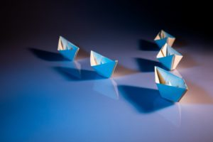 one paper boat leading four other paper boats